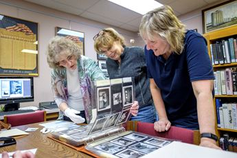 Ladies looking at photos for preservation project