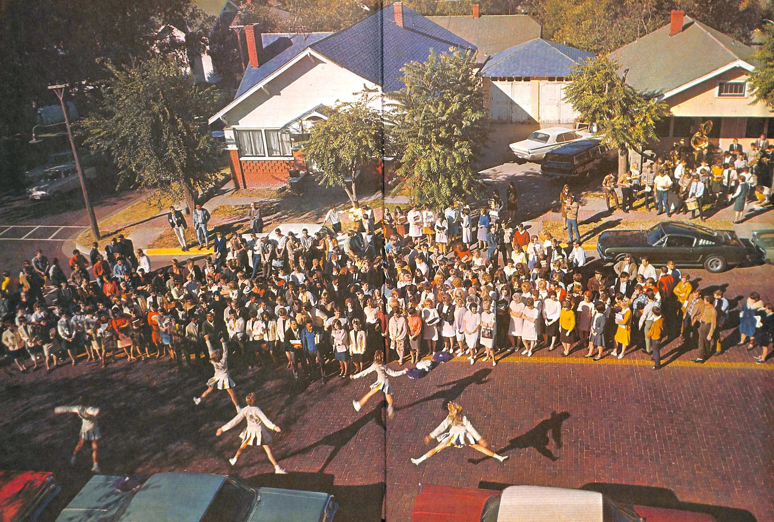 A yearbook photo of a pep rally on a Dodge City street. Cheerleaders jump in the foreground while a large crowd looks on.