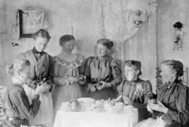 women sitting around table peeling fruit