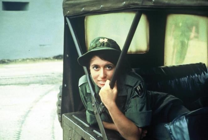A woman in military attire looks at the camera from a vehicle.
