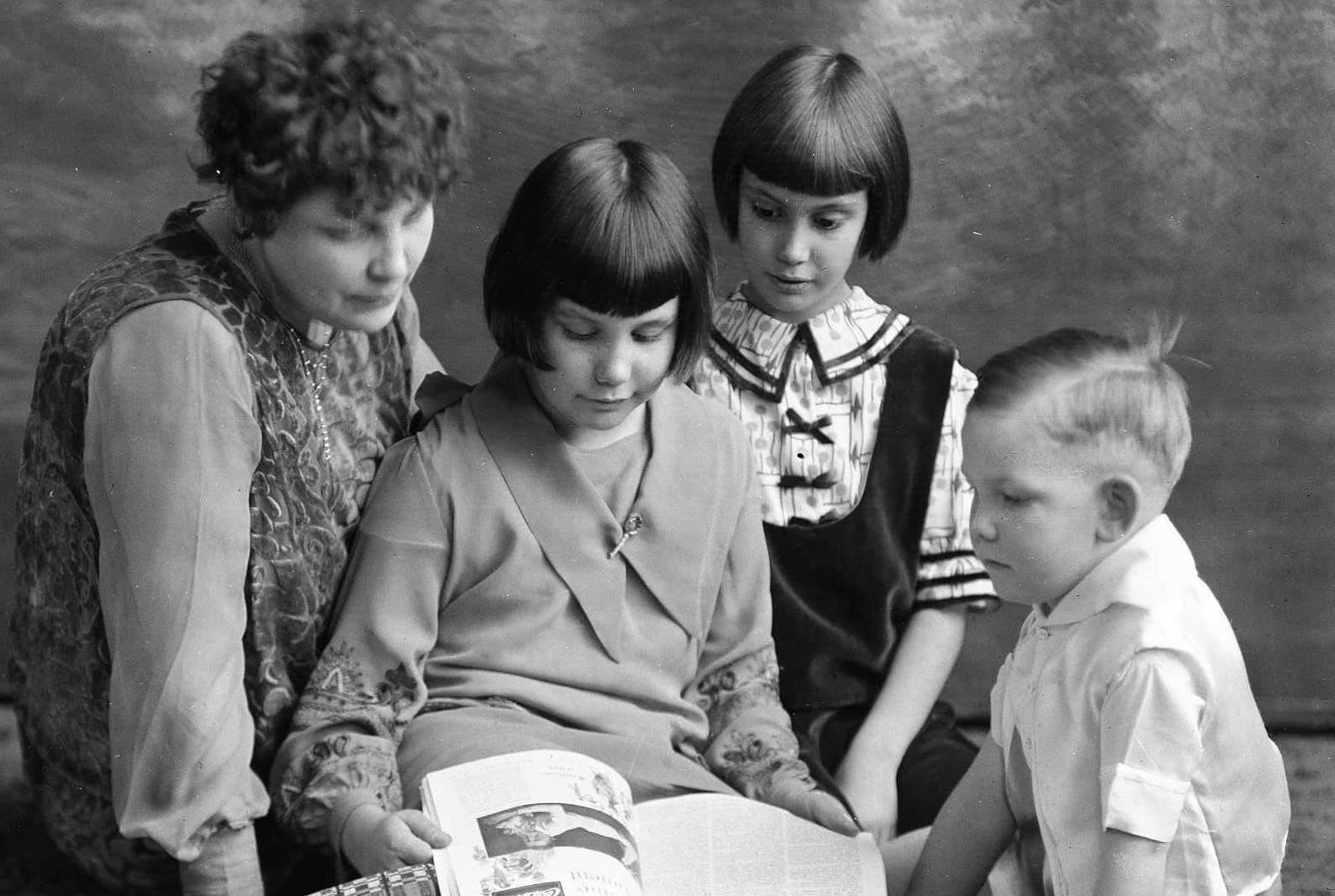 mother and children looking at magazine