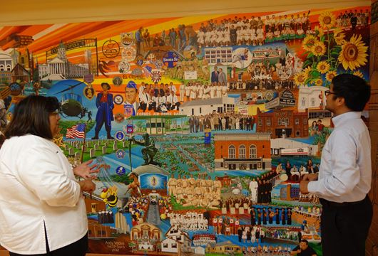 Man and woman talking in front of mural depicting Mexican American history in Topeka