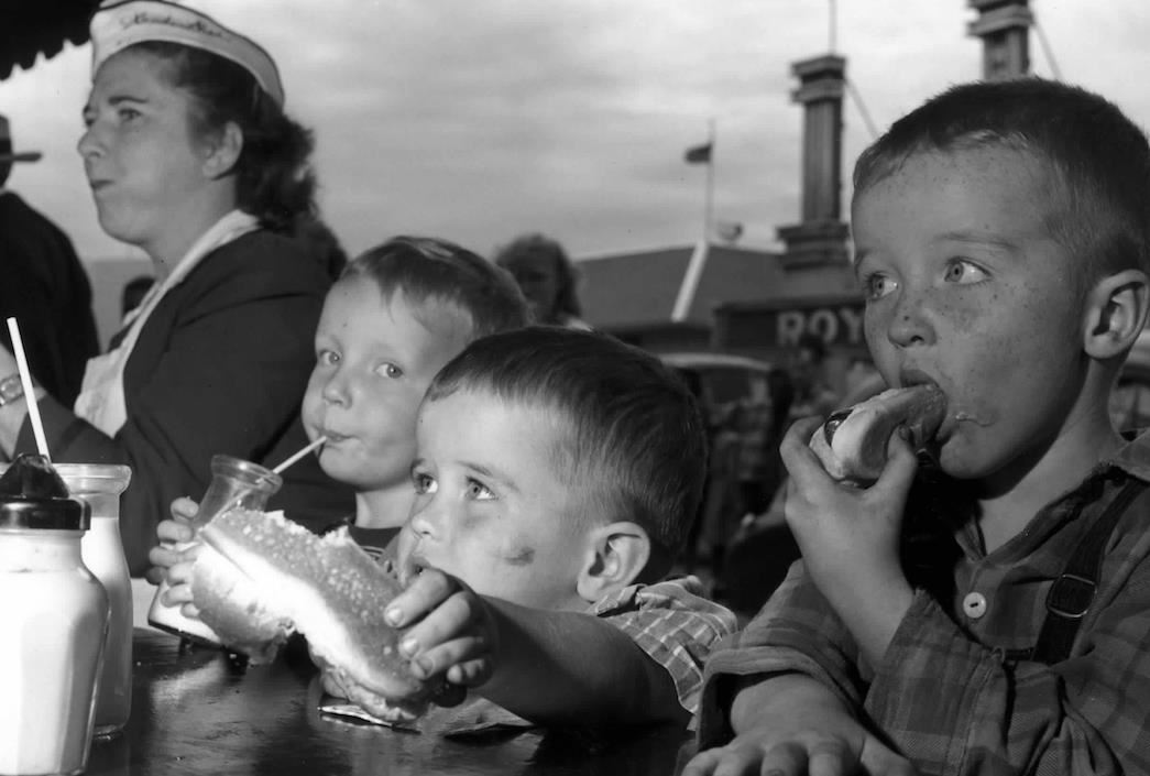 historical photo of children eating hot dogs