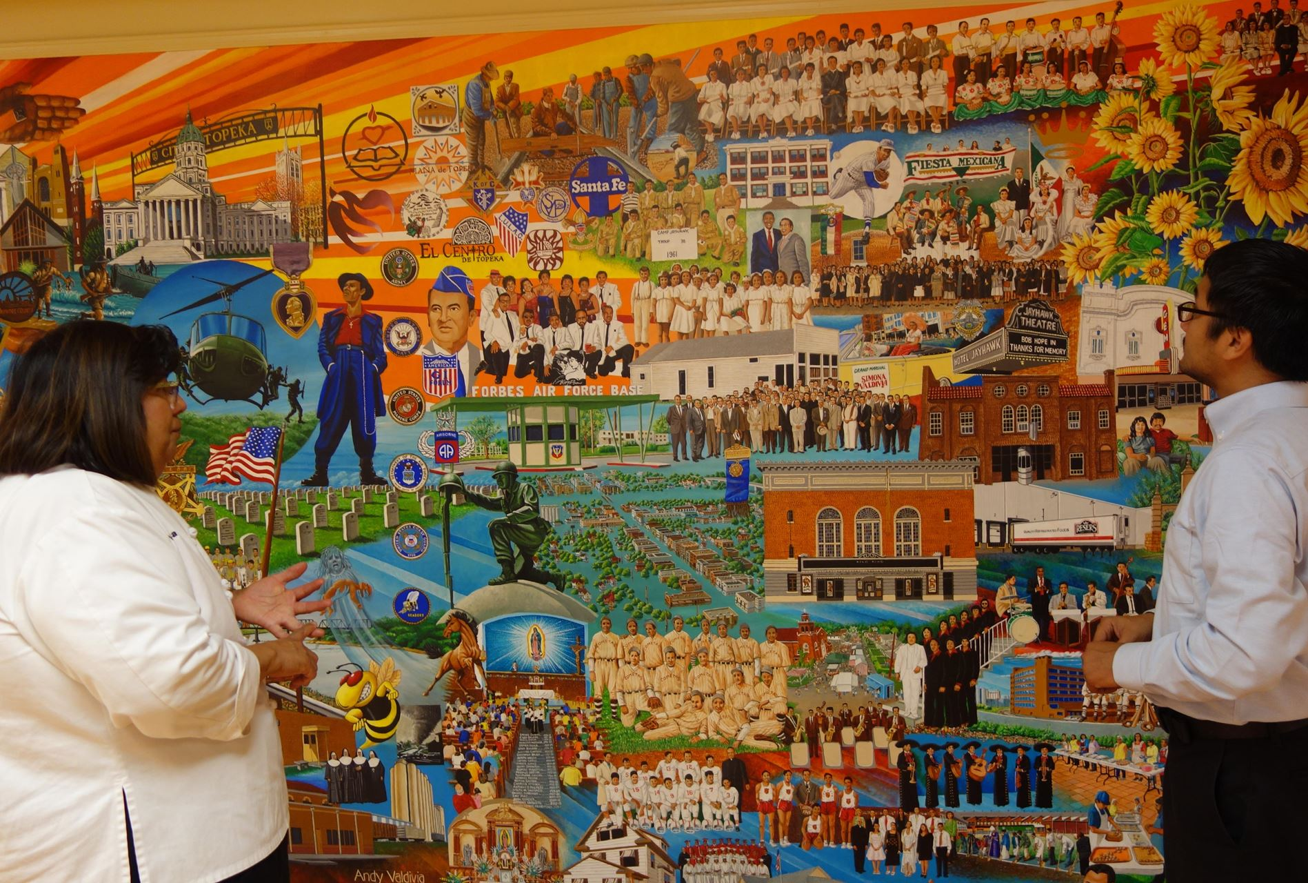 A woman and a man look at the Mexican American Mural in Topeka