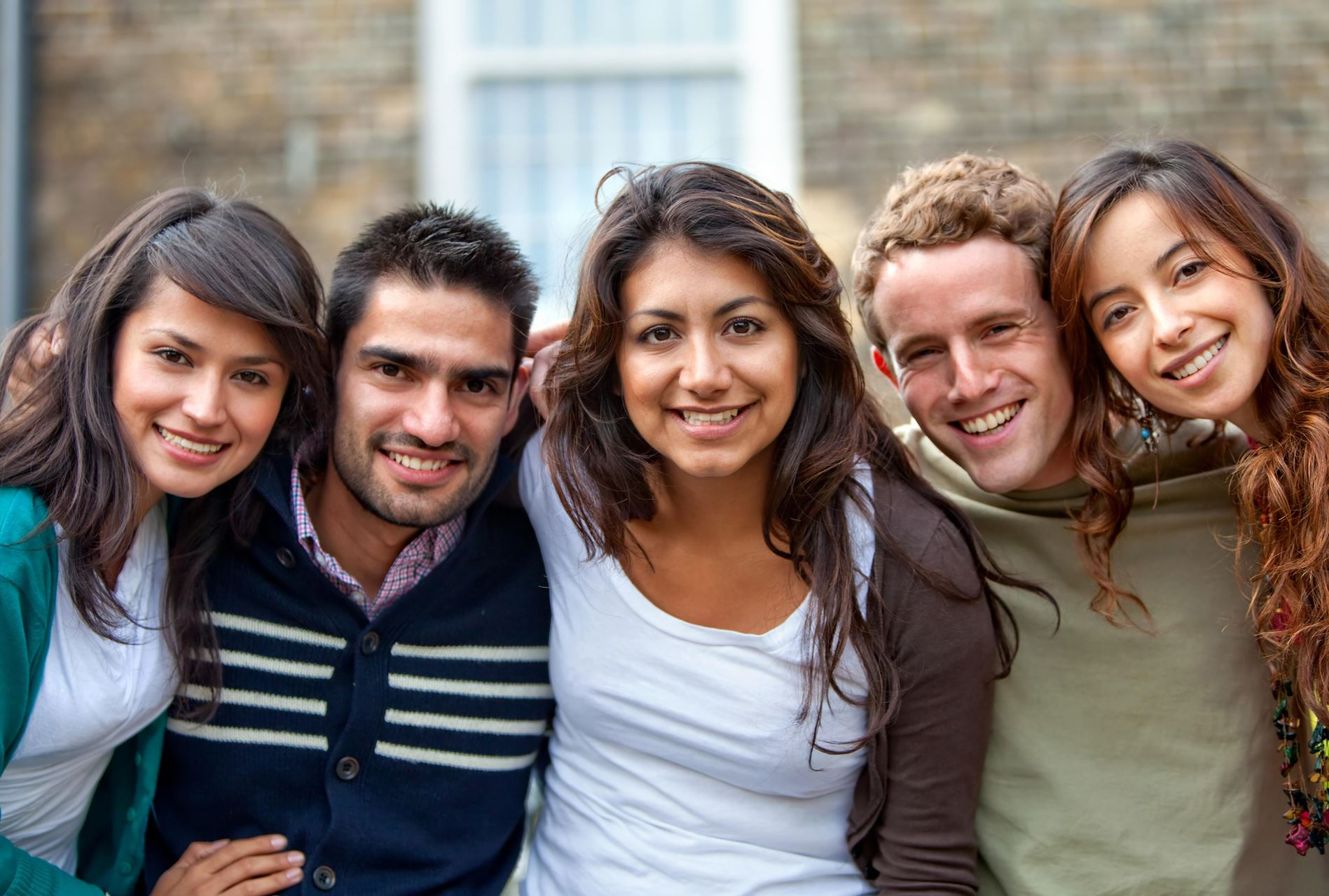 group of young people with their arms linked, smiling