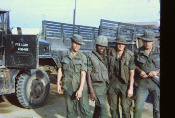 US soldiers in front of supply convoy trucks in Vietnam