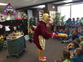 Woman in hen costume speaking to group of children