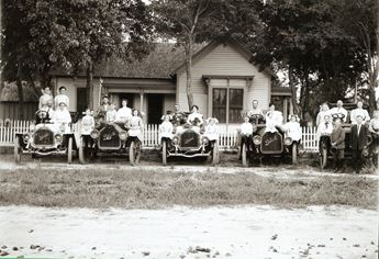 historic photo of people sitting on parked cars in front of a home