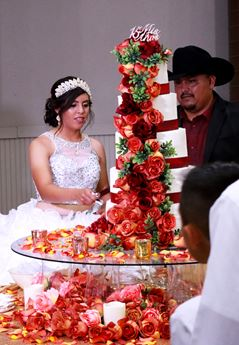 Young girl cuts Quinceañera cake