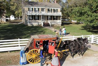 historic farm and stagecoach with people
