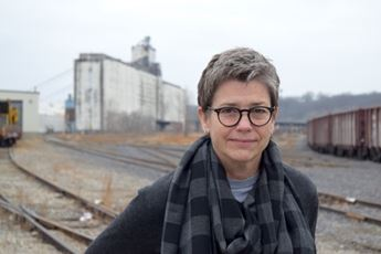 woman in front of a grain silo and train tracks