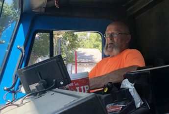 Man sitting in cab of sanitation truck