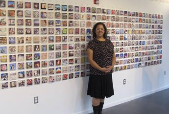 Ann Dean standing in front of exhibition of photographs