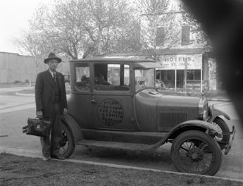 historic photo of man standing by automobile