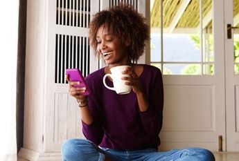 woman looking at phone and drinking coffee