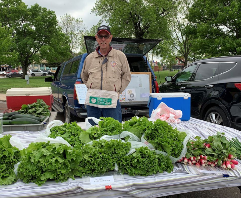 man selling vegetables at a farmers market