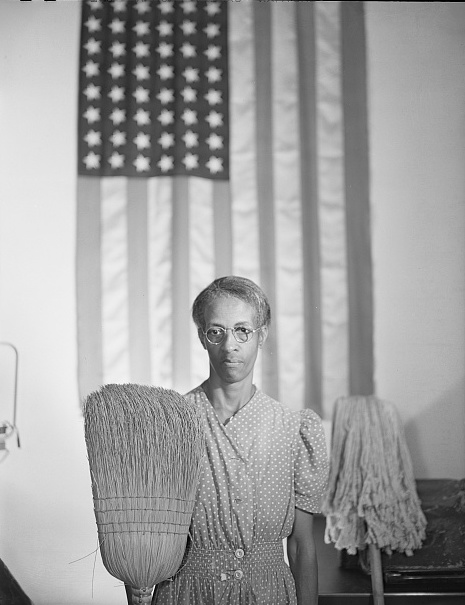 woman holding broom and mop in front of American flag