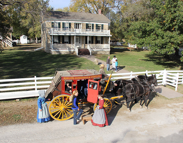historic house with stagecoach and horses in front of it